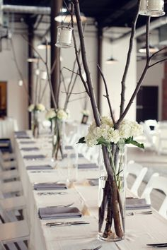 minimal industrial tall centerpiece with branches and hydrangea in a cylinder vase