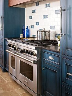 A white backsplash with hand-painted tiles picks up the deep blue of the kitchen cabinets. By mixing blue accent tiles in with the white background, the kitchen gains a charming and handcrafted look. Country Kitchen, New Kitchen, Kitchen Dining, Kitchen Redo, Kitchen Ideas, Dining Room, Black Kitchens, Home Kitchens, Kitchen Black