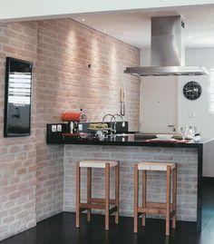 Integrada à sala de estar, a cozinha deste apartamento, oferece à família uma bancada para refeições rápidas. O tampo de Silestone é evidenciado por spots dotados de dicroicas de 50 w (La Lampe), embutidos no forro de gesso, e também recebe a luminosidade vinda da coifa (modelo Letízia) equipada com duas dicroicas de 50 w. Para iluminar a parede de tijolos parecidos com os de demolição, essa mesma lâmpada está nos spots instalados no teto a cada 30cm.