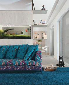 Neste apartamento paulistano, a base clara permite o uso do forte tom de azul e estampas no sofá  e no tapete. O aquário também vira um importante elemento da decor.