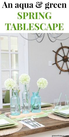 An easy aqua and green coastal tablescape - perfect for a spring brunch or Easter dinner! Love the pretty glass clear and aqua bottles for a centerpiece - they look great on top of that wood cutting board. And that table runner is actually a window valance - genius upcycle! Love the ship wheel on the wall, too, perfect for a coastal dining room! #coastaldecor #coastalfarmhouse #diningroom #diningtable #springstyle #farmhousedecor #farmhousediningtable #centerpieces #tablescapes
