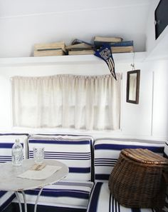 """Frankie"" has a beach feel with the awning striped cushions and vintage books on the shelf."