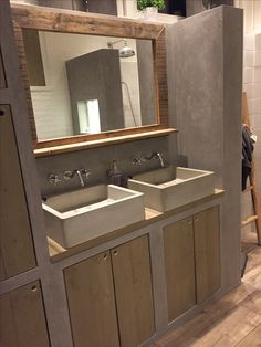 Badkamer met betonnen wasbakken, deurtjes van steigerhout. Betonlook op de muren. Spiegel gemaakt van sloophout. Op de vloer houtlook vloertegels.