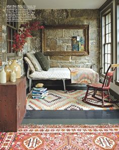 Hmmm ... read or stare out wonderful huge mullioned window??  Love stone walls and vintage metal cots.