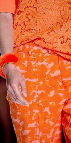 Orange lace top, camo pants and fuzzy bangle.