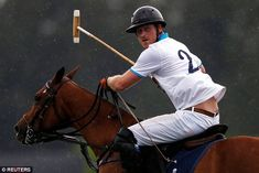 Reminder of home! Harry plays polo in the rain during the Sentebale Royal Salute Polo Cup in Wellington, Florida