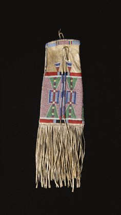 CROW BEADED AND FRINGED HIDE TOBACCO BAG of tapering form, the lower section with a broad beaded panel, with stylized hourglass designs, the reverse with a pair of crosses, trimmed above and below with strips of  red and dark blue wool cloth, triangles spot-stitched on the hide ground; bead-wrapped thongs below the opening.