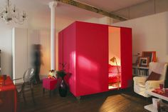 """If you're fortunate enough to have an open loft space but aren't sure what to do for a bedroom, how about a rolling cube just large enough to fit a bed?"" I love this idea, especially in hot pink."