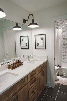 Subway tile kids bathroom. White walls. Gray floors. Benjamin Moore Swiss coffee. Cambria Whitehall. Delta faucets. Black and white. Farm lights. Modern rustic farmhouse.