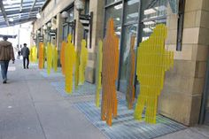 TransitStory showcases 30 steel sculptures of people on the Centre Street transit platform.