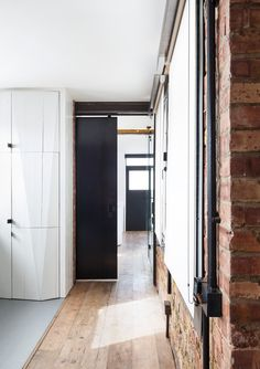 exposed brick wall and painted white reclaimed wooden railway sleepers in corridor by Nathalie Priem interiors photographer