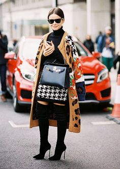 Miroslava Duma in a pair of sleek black suede thigh-high boots and patterned oversized sweater coat.