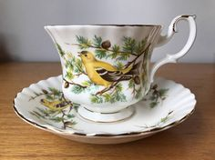 Royal Albert Vintage Teacup and Saucer Pattern: Goldfinch Series: Woodland  This is a beautiful montrose shaped teacup and saucer trimmed in gold. This set has beautiful yellow and black finches perched on pine tree branches. The branches have brown pinecones too. This is a very collectible series, this is one of a series of six! (the other 5 are: Robin, Blue Jay, Hummingbird, Redwing and Baltimore Oriole)  Made in England Fine Bone China Back Stamp dates: 1980-87  Measurements Cup(not…