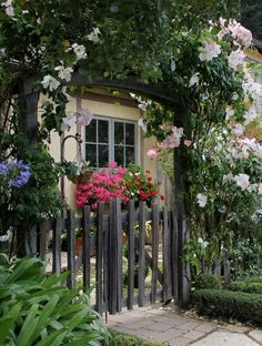beautiful cottage entrance with picket fence, rose covered arbor, broken stone path.  love