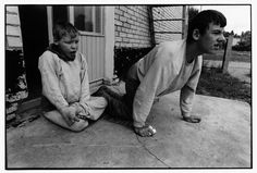BELARUS. 1997. Novinki Asylum, Minsk. Two boys who are not able to walk, pause before they crawl off to join their friends in the yard.  Paul Fusco/Magnum Phots