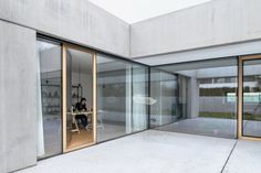 Arhitektura d.o has designed a concrete house in Ljubljana around a central courtyard that connects its living spaces with a ceramics studio. Architecture Site Plan, Space Architecture, Atrium House, Wooden Panelling, Smooth Concrete, Concrete Finishes, Concrete Facade, Tower Block, Paved Patio
