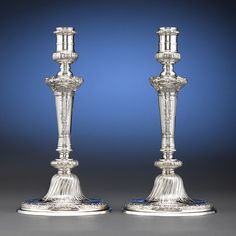 An outstanding pair of sterling silver candlesticks by English silversmith Alexander Johnston. Reflecting the mid-18th century Georgian taste for the Rococo style, these candlesticks feature deeply chased decoration, from shells and palms to acanthus and rosettes, as well as an engraved armorial on each pedestal. Their exuberant yet balanced design is characteristic of the sophisticated style brought to England by French Huguenot silversmiths in the 1700s. Alexander Johnston first entered…