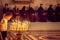 A little boy blowing out the candles in the Church of Holy Sepulchre, Jerusalem