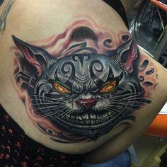 shoulder blade chesire cat tattoo evil