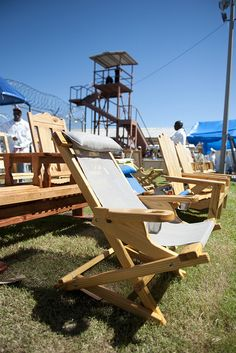 hand crafted wooden chairs & benches at the crafts fair of the Angola Prison Rodeo in Louisiana on October 2, 2011 with the prison watch tower very close by.