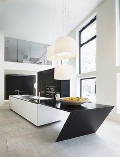 Une cuisine ouverte noire et blanche avec un îlot ultra moderne. http://www.m-habitat.fr/amenagement/ilot-central/bien-choisir-son-ilot-de-cuisine-426_A
