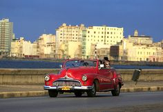 Daily life in Cuba   Car drives on Havana´s seafront boulevard El Malecon.