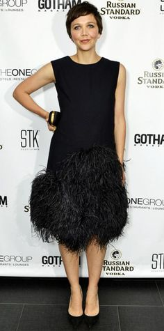 JUNE 27, 2013 Maggie Gyllenhaal WHAT SHE WORE Gyllenhaal played up her red carpet look in a dark sleeveless Dries Van Noten shift with an amazing feathered hem. A black-and-gold minaudiere and black Casadei pumps completed the look.