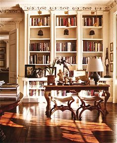 This is how Bill Blass styled library shelves. There are some collections in shelves on their own, keeping the books from being overwhelming. I especially like the articulated brass library lights.