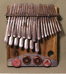 Mbira-- is an African musical instrument consisting of a wooden board (often fitted with a resonator) with attached staggered metal tines, played by holding the instrument in the hands and plucking the tines with the thumbs. The mbira is usually classified as part of the lamellaphone family, and part of the idiophone family of musical instruments.
