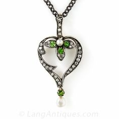 Dating from the turn-of-the-last century, a delightful, artfully stylized heart pendant, hand-fabricated in silver over gold, glistens with small rose-cut diamonds, four vibrant green demantoid garnets and a dangling freshwater pearl. A sweetheart. 1 1/2 inches by 3/4 inch; the newer silver chain measures 18 inches.
