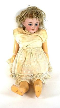 A German bisque headed doll With blonde wig, open/shut blue