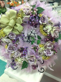 spring, kids light purple feather boa wraped around wood ring....spring flowers glued on, resting in plate stand.