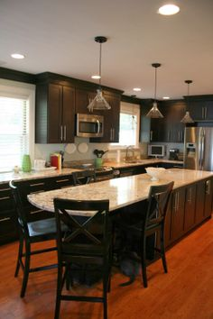 Dark/black cabinets with reddish flooring Long narrow island
