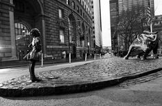 A new bronze statue of a fearless girl faces Charging Bull in Bowling Green Park in Lower Manhattan.