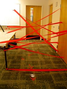 """A black balloon """"mine"""" field, red crepe paper lasers, and mini marshmallow flinging catapults that the kids make for a spy themed party. Spy Training Academy"""