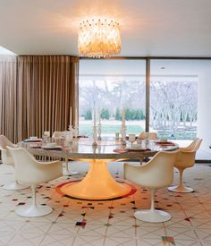 The dining room centers around a custom Saarinen-designed marble-and-terrazzo table ringed by Tulip chairs. Overhead is a Venini chandeli...