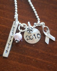 """Surviving a cancer or illness, one of life's most severe challenges, is a reason to celebrate! This necklace symbolizes the triumph survivors faced and allows them to show support for their special cause and celebrate life at the same time!    This sterling silver necklace features one Avery Charm stamped with """"Survivor,"""" Awareness Ribbon accent charm, small classic circle charm stamped with the year and your color choice of crystal dangle."""