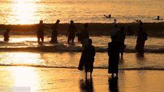 People swimming in Arabian sea during sunset