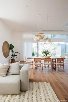 minimalist living and dining room with wood floors and table and chairs and a beige sofa and rug