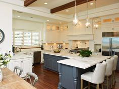 A kitchen this large allows designers to really get creative with the layout as designer Kari Arendsen has here by wrapping the walls in white cabinets then creating a huge L-shaped island to provide prep space and a spot for the family to gather for quick meals. The island's steely blue color helps to anchor the space and breaks up what otherwise would have been a lot of white cabinets.