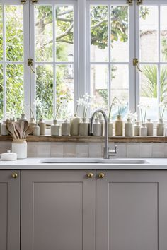 Interior Design by Imperfect Interiors at this Georgian terraced house in London. A palette of calm Farrow & Ball paint colours mixed with traditional details. Moroccan Zellige tiles, a rustic wooden window sill, wooden casement windows with brass handles and composite worktop make this Shaker kitchen the perfect blend of old and new. Photo by Chris Snook