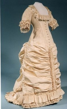 Wedding Dress, 1881, silk, London.  Cream ribbed silk trimmed with cream lace. The bodice is boned and the tight sheath-like style is achieved by Drawstrings in a back section of the skirt to give a soft bustle effect. This style, elaborately trimmed with ruching and pleated flounces is in the latest fashion. The square neck has later been lowered for evening wear. Before 1886 marriages had to take place before 12 noon and low necklines were not considered suitable for morning wear.