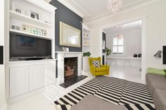 white floorboards, corner sofa, modern black and white rug, grey feature chimney breast, victorian terrace