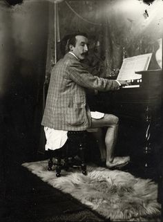 French artist, Paul Gauguin, playing a parlour organ in Czech art nouveau artist, Alphonse Mucha's studio in paris in 1893. Looks to be wearing just a nightshirt with a jacket. Photo by Mucha.