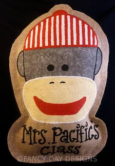 Adorable sock monkey themed teacher door sign or birthday door hanger that is perfect for your classroom or party decor.  This sock monkey is hand painted on burlap and may be completely customized if you prefer. Your preference of wording is written in black below the monkeys head. The burlap is lightly stuffed and has a ribbon attached on the back so that it can be easily hung or placed around the home for decoration. Burlap edge will have a slightly rustic edge.  Item is approximately 14…