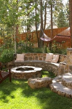Stone wall seating area and fire pit. Would love to have something like this in my back yard. One day!