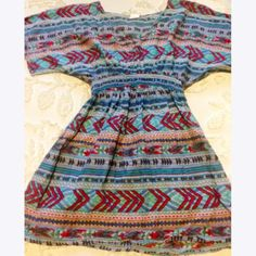 Aztec Tunic Top Gorgeous and colorful v-neck tunic styled top with Aztec pattern. Flowy and thin perfect for a summer out! Depending on your height could also make for a shorter dress. Never worn, size small. Tops Tunics