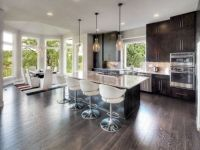 View of the kitchen and dining room in this contemporary modern designed home with dramatic light fixtures, vaulted ceiling, amazing views off of the rear of the home, and dark stained hardwood floors.