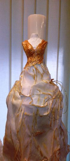 A wedding candle  with a styrofoam bust decorated with silk cotton fabric hardened with ivory color  powertex,  gold patina and  a golden metallic  butterfly.
