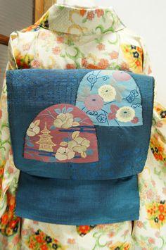 趣深い藍の地に、ただよう霞に佇む小塔と椿、梅と菊花が美しくのぞく小窓のようなモチーフが織り出された紬の名古屋帯です。